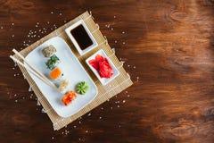 Sushi réglés sur un fond en bois foncé images stock
