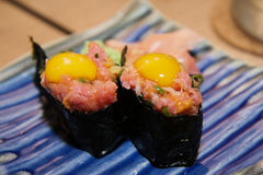 Sushi raw tuna choped with raw Quail eggs. Fresh and raw many kind of Japanese fish on the rice is the Japanese traditional food in the decorated container Royalty Free Stock Photos