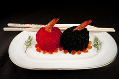 Sushi  with red and black fish eggs. Sushi covered with red and black fish eggs garnished with dill and surrounded by salmon roe Stock Image