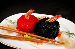 Sushi, red and black fish eggs with chopsticks.. Sushi covered with red and black fish eggs garnished with dill and surrounded by salmon roe, shrimp, wasabi and Stock Photos