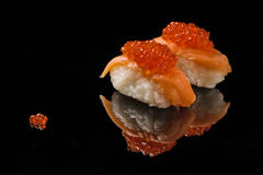 Sushi and red caviar on black acryle Royalty Free Stock Images