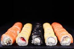 Sushi restaurant menu, maki rolls set. Seafood restaurant menu, professional culinary, Japanese food art. appetizing maki sushi set, served on black stone slate stock image
