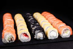 Sushi restaurant menu, maki rolls set. Seafood restaurant menu, professional culinary, Japanese food art. appetizing maki sushi set, served on black stone slate royalty free stock photos