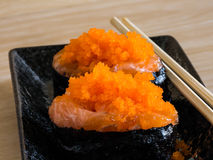 Sushi rice wrapped in seaweed and shrimp egg on a wooden table. Stock Photos