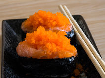Sushi rice wrapped in seaweed and shrimp egg on a wooden table. Royalty Free Stock Photos
