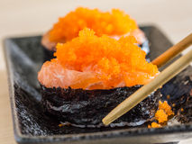 Sushi rice wrapped in seaweed and shrimp egg on wooden table. Royalty Free Stock Photo