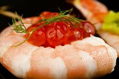 Sushi rodado de la gamba con las huevas de color salmón. Fotografía de archivo