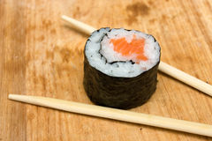 Sushi roll. Closeup of sushi roll with salmon on cutting board Royalty Free Stock Image
