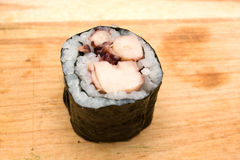 Sushi roll. Closeup of sushi roll with octopus on cutting board Stock Photography