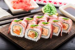 Sushi roll with bacon. Salmon teriyaki, tomato and lettuce Stock Images