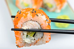 Sushi roll with black chopsticks Stock Photos