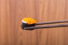 Sushi roll with black chopsticks Stock Images