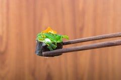 Sushi roll with black chopsticks Stock Photos