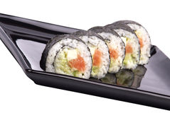 Sushi - Roll on a black plate isolated Royalty Free Stock Images