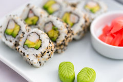 Sushi Roll- California Roll-Japanese Food. Japanese food Sushi Roll, californian style with black and white sesame on a white dish with green wasabi and ginger Stock Image