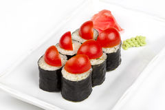 Sushi roll with cherry tomatoes and cheese. On plate Royalty Free Stock Photo