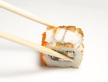 Sushi roll and chopsticks Stock Images