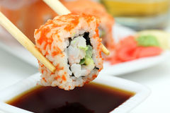 Sushi roll in chopsticks Royalty Free Stock Photos