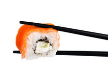 Sushi roll in chopsticks Isolated. On white Royalty Free Stock Images