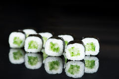 Sushi Roll with cucumber over  black background with reflection. Sushi Roll with cucumber over  black background Stock Images