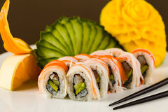 Sushi Roll. Fancy California crab roll with avocado on a white plate garnished with sliced cucumber, orange and carved mango Royalty Free Stock Images