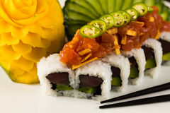 Sushi Roll. Fancy spicy tuna roll roll with avocado and jalapeno pepper on a white plate garnished with sliced cucumber and carved mango Stock Photography