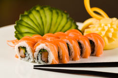 Sushi Roll. Fancy  tuna and salmon roll  on a white plate garnished with sliced cucumber and fruit carving Royalty Free Stock Photography