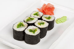 Sushi roll with fish and green salad. Sushi roll with fish and green salad on plate Stock Image