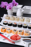 Sushi roll healthy food - japanese style. Various kinds served on white plate against the background of orchid Stock Photo