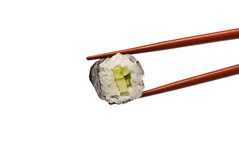 Sushi Roll is held by Chopsticks Stock Photography