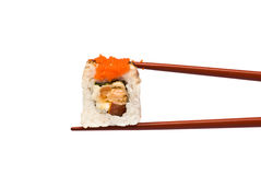 Sushi Roll is held by Chopsticks Royalty Free Stock Photography