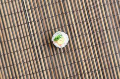 Sushi roll lie on a bamboo straw serwing mat. Traditional Asian food. Top view. Flat lay minimalism shot with copy space.  stock photo