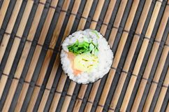 Sushi roll lie on a bamboo straw serwing mat. Traditional Asian food. Top view. Flat lay minimalism shot with copy space.  royalty free stock photo