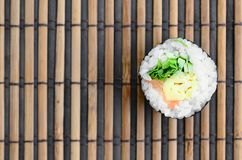 Sushi roll lie on a bamboo straw serwing mat. Traditional Asian food. Top view. Flat lay minimalism shot with copy space.  stock image