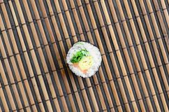 Sushi roll lie on a bamboo straw serwing mat. Traditional Asian food. Top view. Flat lay minimalism shot with copy space.  stock photos