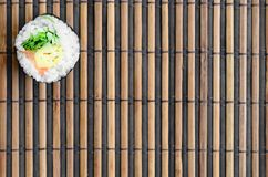 Sushi roll lie on a bamboo straw serwing mat. Traditional Asian food. Top view. Flat lay minimalism shot with copy space.  royalty free stock photography