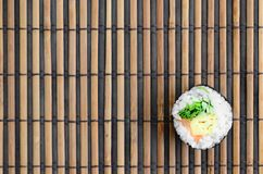 Sushi roll lie on a bamboo straw serwing mat. Traditional Asian food. Top view. Flat lay minimalism shot with copy space.  stock images