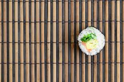 Sushi roll lie on a bamboo straw serwing mat. Traditional Asian food. Top view. Flat lay minimalism shot with copy space.  royalty free stock images