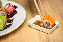 Sushi roll made dish assorti. Chopsticks with roll, nut souce Stock Image