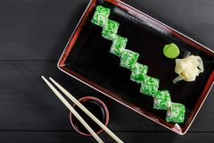 Sushi Roll - Maki Sushi with green caviar, Crab meat, avocado and cream cheese on dark wooden background. Top view. Japanese cuisine royalty free stock photos