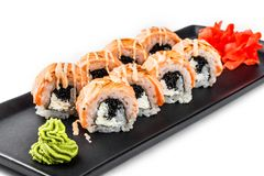 Sushi Roll - Maki Sushi made of grilled salmon, black caviar and cream cheese on black plate isolated over white background stock images