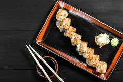 Sushi Roll - Maki Sushi made of salmon, cucumber, avocado and cream cheese on dark wooden background. Top view. Japanese cuisine royalty free stock photo