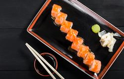 Sushi Roll - Maki Sushi made of salmon, cucumber, avocado and cream cheese on dark wooden background. Top view. Japanese cuisine stock photo