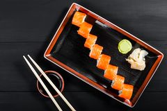 Sushi Roll - Maki Sushi made of salmon, cucumber, avocado and cream cheese on dark wooden background. Top view. Japanese cuisine stock photography