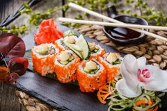 Sushi Roll - Maki Sushi made of Salmon, Red caviar, cucumber. Avocado and cream cheese on black stone on bamboo mat decorated with flowers. Japanese cuisine royalty free stock images