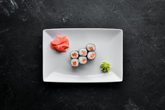 Sushi roll maki with salmon. Japanese cuisine. Top view. On a black stone background royalty free stock photos