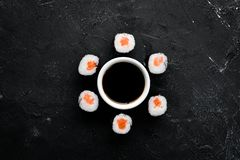 Sushi roll maki with salmon. Japanese cuisine. Top view. On a black stone background royalty free stock image