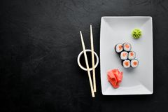 Sushi roll maki with salmon. Japanese cuisine. Top view. On a black stone background stock image