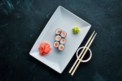 Sushi roll maki with salmon. Japanese cuisine. Top view. On a black stone background stock photography