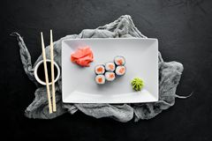 Sushi roll maki with salmon. Japanese cuisine. Top view. On a black stone background stock photo